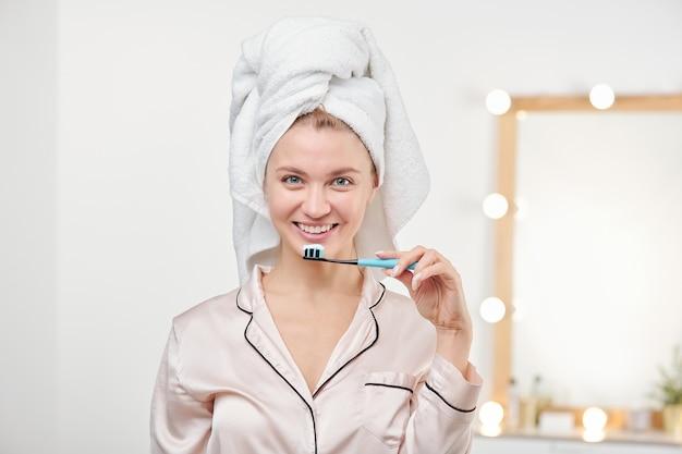 Donna abbastanza giovane che tiene lo spazzolino da denti dalla sua bocca