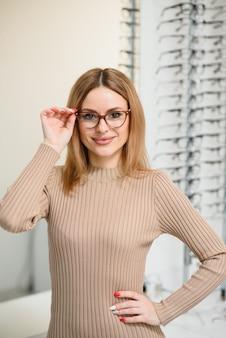 La donna abbastanza giovane sta scegliendo nuovi occhiali al negozio di ottica