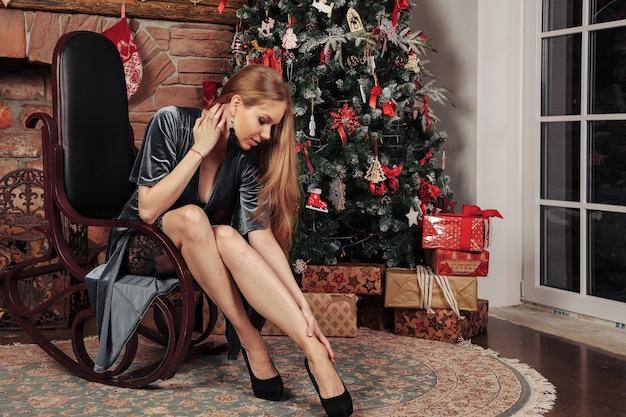 Piuttosto giovane donna è seduta vicino all'albero di natale con soggiorno decorato con camino. la femmina è circondata da decorazioni e regali di natale. concetto di accogliente celebrazione del nuovo anno. copia spazio