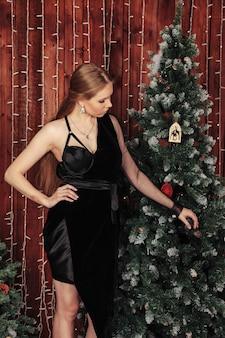 La giovane donna graziosa sta facendo una pausa l'albero di natale con il salone decorato in vestito nero. la femmina è circondata da decorazioni natalizie. concetto di accogliente celebrazione del nuovo anno. copia spazio