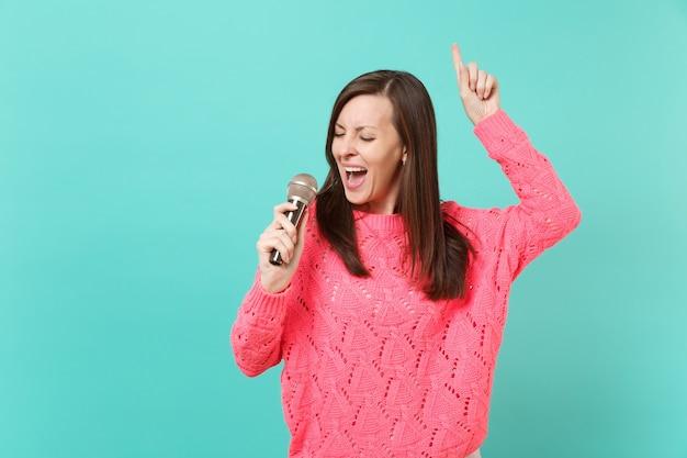 Bella giovane donna in maglione rosa lavorato a maglia che balla, puntando il dito indice in alto, canta una canzone nel microfono isolato su sfondo blu muro, ritratto in studio. concetto di stile di vita della gente. mock up copia spazio.