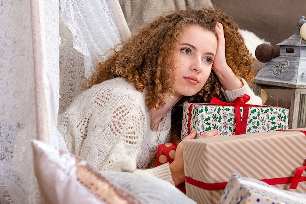 La giovane donna graziosa che pone sulle scatole regalo di natale indossa il pullover lavorato a maglia bianco