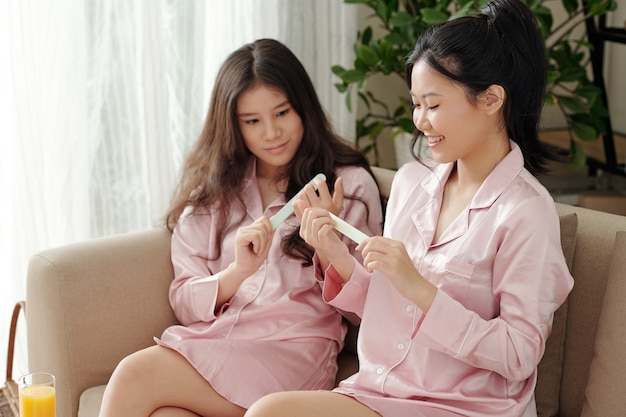Piuttosto giovane donna che impara da un amico, limando e lucidando le unghie e ripetendo dopo di lei