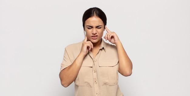 Piuttosto giovane donna che sembra arrabbiata, stressata e infastidita, coprendo entrambe le orecchie con un rumore assordante, un suono o una musica ad alto volume