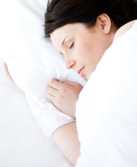 Giovane donna graziosa che si trova in un letto che dorme