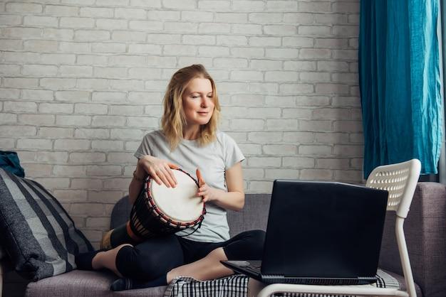 La giovane donna graziosa fa musica suonando il djembe, guardando il portatile. corso online remoto di suonare il tamburo