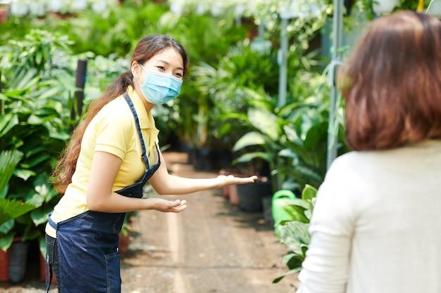 Bella giovane donna in maschera medica che accoglie i clienti nel vivaio