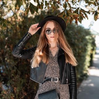Modello abbastanza giovane donna in abiti neri alla moda con abito vintage, giacca di pelle, occhiali da sole, cappello e borsetta passeggiate nella soleggiata città autunnale vicino agli alberi