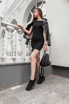 Modello di donna abbastanza giovane con borsa in un abito corto alla moda in una giacca di pelle nera in scarpe da ginnastica alla moda in posa vicino a un edificio bianco vintage. ragazza attraente moderna sexy. moda giovanile. autunno.