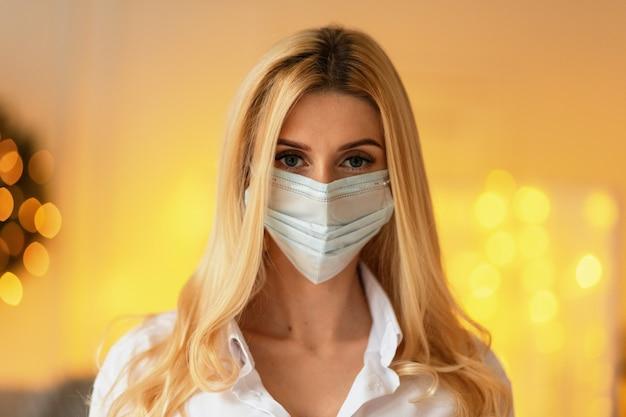 Modello di donna abbastanza giovane con una maschera protettiva medica in una camicia bianca su uno sfondo di luci gialle al chiuso.