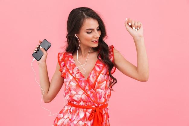Bella giovane donna in posa muro isolato utilizzando il telefono cellulare ascoltando musica con gli auricolari.
