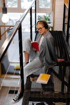 Donna abbastanza giovane che legge in biblioteca