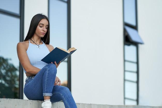 Una donna abbastanza giovane legge un libro fuori dal college