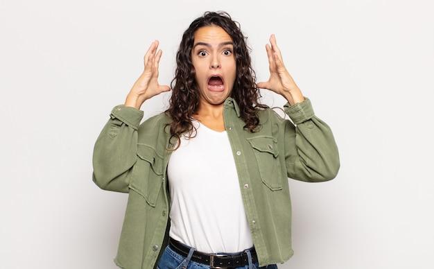 Piuttosto giovane donna che grida con le mani in alto in aria, sentendosi furiosa, frustrata, stressata e sconvolta