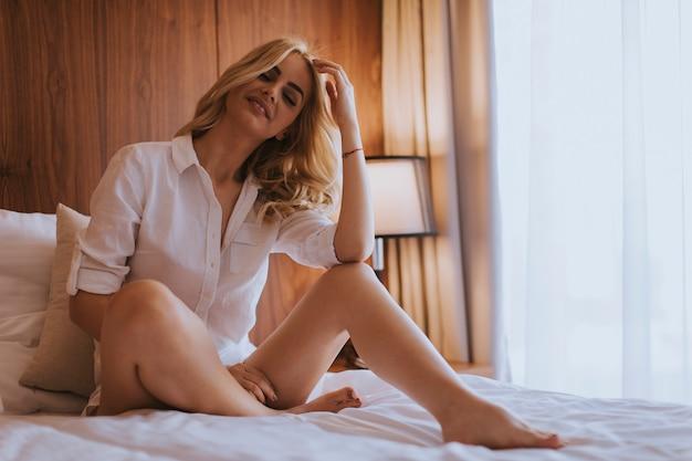 Bella giovane donna seduta sul letto in camera