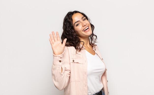 Bella giovane donna che sorride allegramente e allegramente, agitando la mano, dandoti il benvenuto e salutandoti o salutandoti