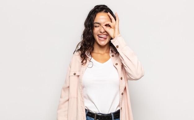 Bella giovane donna sorridente felicemente con una faccia buffa, scherzando e guardando attraverso lo spioncino, spiando i segreti