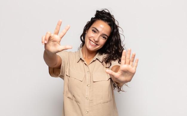 Piuttosto giovane donna sorridente e guardando amichevole, mostrando il numero otto o ottavo con la mano in avanti, conto alla rovescia