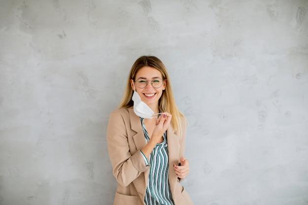 Piuttosto giovane donna in piedi accanto al muro grigio e si toglie una maschera respiratoria dal coronavirus