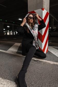 La giovane donna graziosa in vestiti alla moda mette la sciarpa di seta dell'annata sulla testa all'aperto. la ragazza alla moda in occhiali da sole scuri in capispalla neri alla moda posa vicino alla colonna a strisce rosso-bianche sulla città. eleganza.