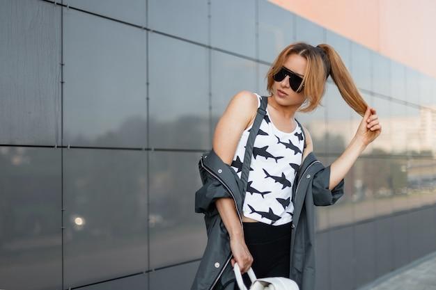 Bella giovane donna in elegante t-shirt bianca con un motivo in una giacca vintage con uno zaino in pelle in occhiali da sole in posa sulla strada vicino a un edificio moderno grigio in una luminosa giornata estiva.