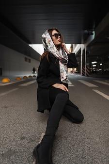 Bella giovane donna in occhiali da sole in elegante cappotto nero con sciarpa di seta elegante sulla testa in stivali in jeans si siede sull'asfalto nel parcheggio in strada. il modello di moda urbano della ragazza americana riposa all'aperto.