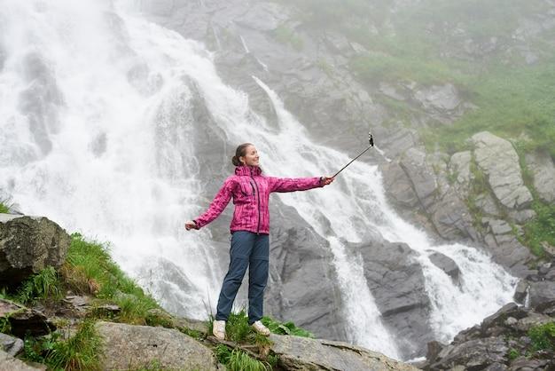 Giovane donna graziosa che prende un selfie davanti alla grande cascata potente. bello viaggio sorridente della ragazza in natura. concetto di viaggio e svago.