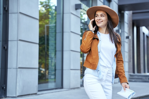 Piuttosto giovane donna parlando al cellulare e tenendo la mappa della città. concetto di stile di vita