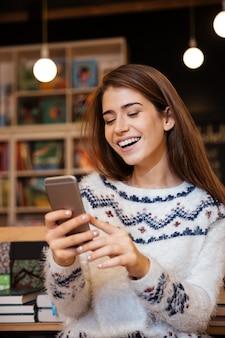 Bella giovane donna che manda un sms al cellulare mentre è seduta in biblioteca e ride