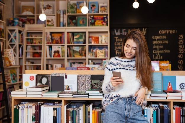Bella giovane donna che manda un sms al cellulare mentre è seduta in biblioteca