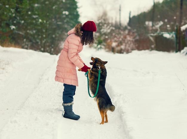 Bella giovane donna che addestra il suo cane in inverno