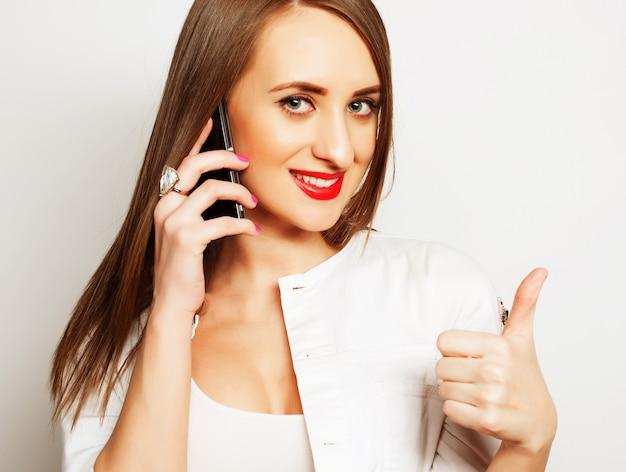 Piuttosto giovane donna che utilizza il telefono cellulare su sfondo bianco Foto Premium