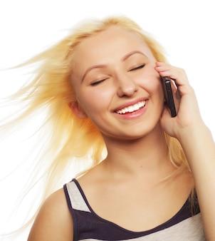 Bella giovane donna che utilizza il telefono cellulare su sfondo bianco