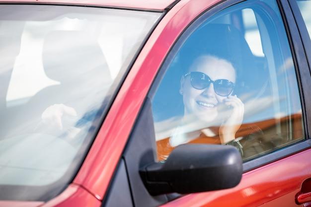 Piuttosto giovane donna che utilizza uno smart phone, cellulare mentre si guida un'auto, concetto di trasporto