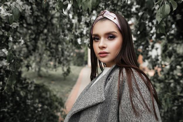 Bella giovane donna in bandana vintage in cappotto grigio alla moda vicino a fogliame verde nel parco. modello di moda ragazza carina in abiti alla moda passeggiate e gode di natura di bellezza. la signora splendida si diverte all'aperto.
