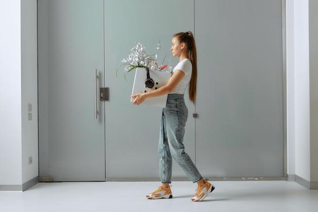 Una bella giovane donna cammina con gli articoli per ufficio in una scatola, triste, dopo essere stata tagliata e licenziata a causa della crisi.