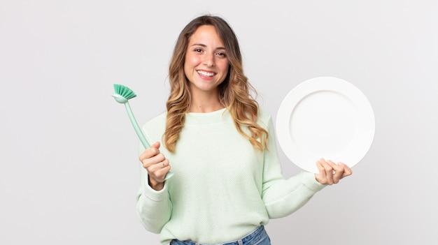 Concetto di lavaggio dei piatti della donna abbastanza giovane