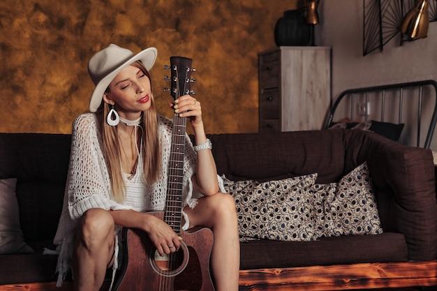 Piuttosto giovane donna in abiti bianchi con la chitarra all'interno del soggiorno. donna carina sul divano con la chitarra. concetto di apprendimento a casa o musica a casa e educazione musicale. copia spazio sito