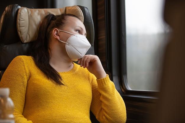 Bella giovane donna con maschera facciale anche un respiratore che viaggia in treno durante la pandemia covid-19, coronavirus, concetto di trasporto transport