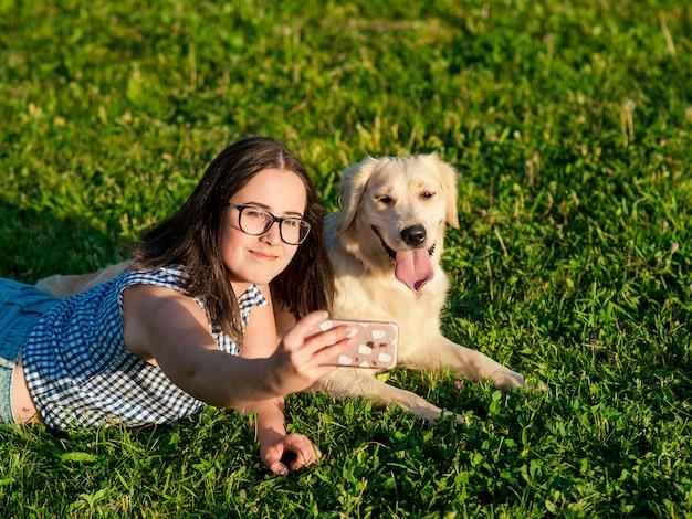 Piuttosto giovane donna con amichevole golden retriever cane prendendo un selfie con uno smartphone.