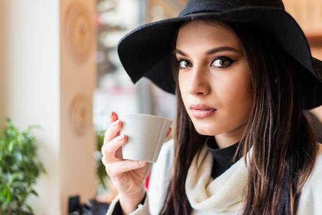 Donna abbastanza giovane con il cappello che beve caffè