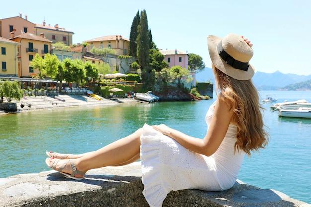 Piuttosto giovane donna con cappello seduto sul muro guardando il bellissimo paesaggio di varenna sul lago di como, italia