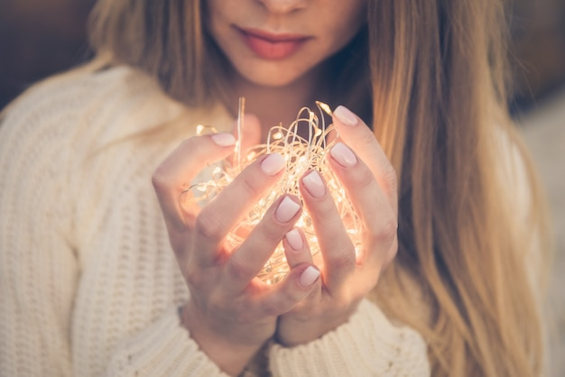 Piuttosto giovane donna con la scintilla magica nelle sue mani a coppa insieme