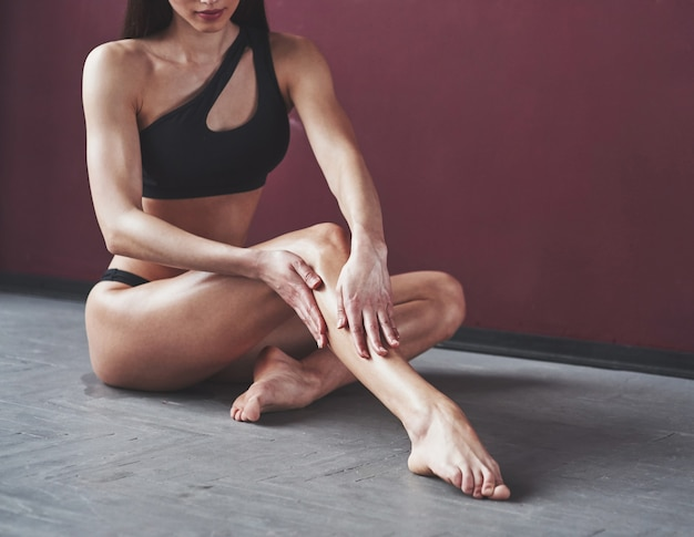 Bella giovane donna con una bella forma del corpo fitness in posa nella stanza
