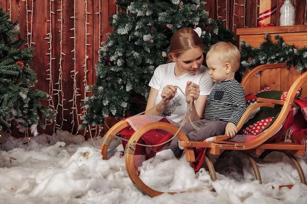 Bella giovane donna con un bambino di un anno che gioca vicino all'albero di natale nel soggiorno. mamma con figlio carino nella stanza decorata di natale. sono sorridenti e felici. concetto di capodanno in famiglia. copia spazio