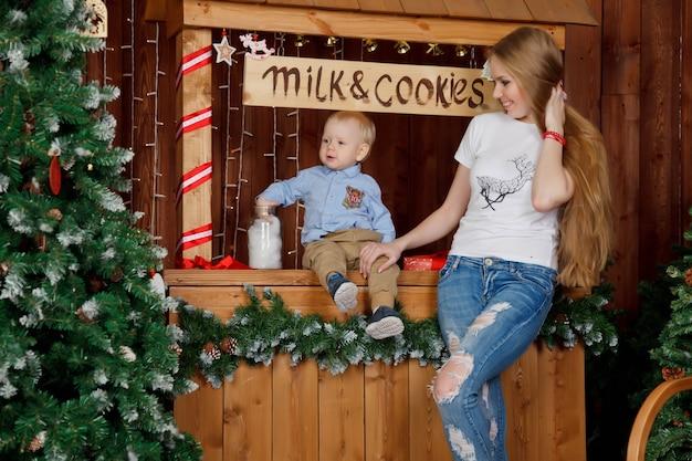 Bella giovane donna con un bambino di un anno al buffet e scritta milk amp cookies
