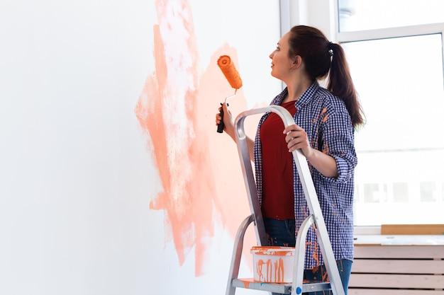 Piuttosto giovane donna con rullo di pittura al chiuso. ristrutturazione, ristrutturazione, riparazione di appartamenti e concetto di ristoro.