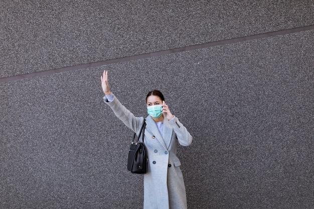 Giovane donna graziosa con la maschera facciale protettiva sulla via