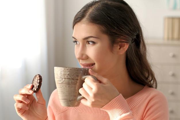 Bella giovane donna con un gustoso biscotto e una tazza di tè a casa