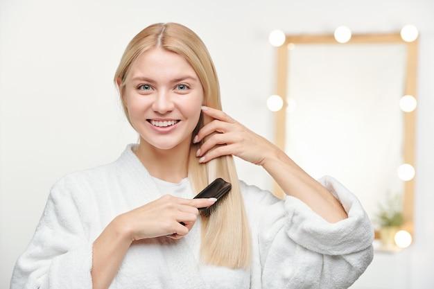Bella giovane donna con un sorriso a trentadue denti spazzolando i suoi lunghi capelli biondi